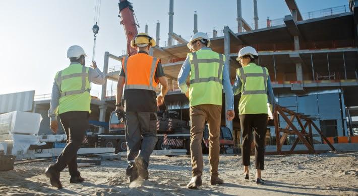 hommes et femmes de dos avec équipement de sécurité sur un chantier de construction