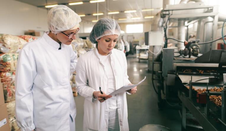 deux femmes en tenue de protection dans une entreprise du secteur alimentaire
